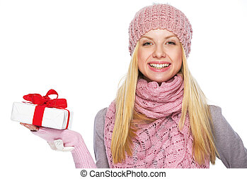 Happy teenager girl in winter hat and scarf showing presenting box