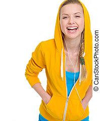 Happy teenager girl listening music in earphones