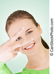 Happy teenager girl showing victory sign