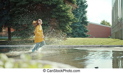 Happy teenager in colorful raincoat and gumboots running in puddles wearing headphones enjoying leisure time activity. Happiness, youth and music concept.
