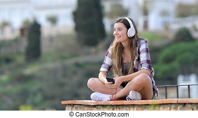 Happy teenager listening to music on vacation