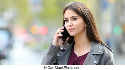 Happy teenager talking on phone in the street with a green background