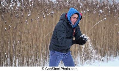 Happy teenager throw snowballs