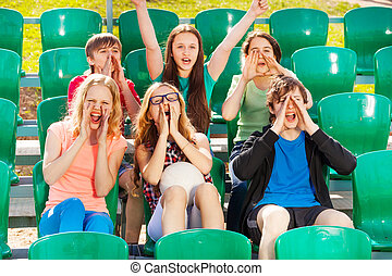 Happy teenagers cheer for the team during game