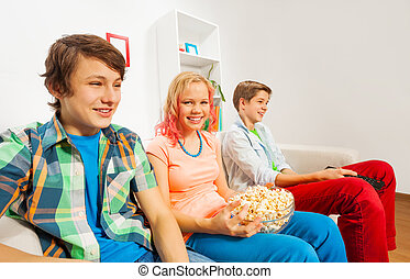Happy teenagers hold popcorn and sit on sofa