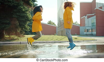 Happy teenagers in raincoats and gumboots are jumping in puddle having fun laughing enjoying leisure time outdoors. People, youth and happiness concept.