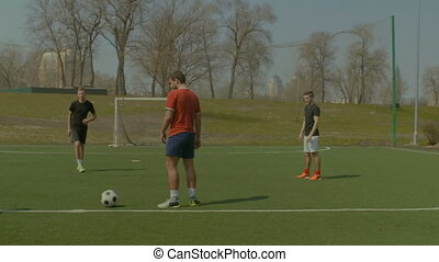 Happy teenagers playing soccer on the field