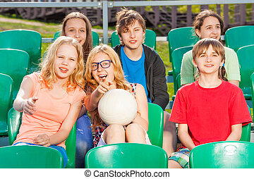 Happy teenagers sitting on the tribune during game
