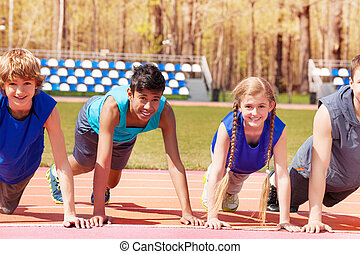 Happy teens doing push-up exercises on the track