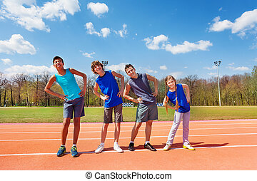 Happy teens doing side bending exercises outdoors - Four...