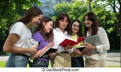 Happy Teens girls Studying Together Outdoors, Enjoying Life. Students books