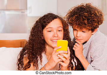 Happy teens with cell phone text on social network