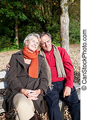 Happy tender senior couple sitting on a bench
