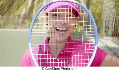 Happy tennis player smiling through her racket