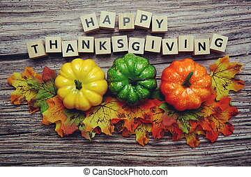 Happy Thanksgiving alphabet letter with pumpkins and autumn leaves on wooden background