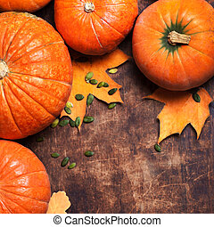 Happy Thanksgiving Card - rustic wood background with a pumpkin and dry autumn leaves