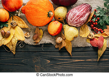 Happy Thanksgiving concept. Beautiful composition of Pumpkin, autumn vegetables with colorful leaves, acorns, nuts, berries on wooden rustic table, flat lay. Space for text. Fall season