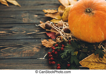 Happy Thanksgiving concept. Beautiful composition of Pumpkin, autumn vegetables with colorful leaves,acorns,nuts, berries on wooden rustic table. Fall seasons greeting card