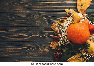 Happy Thanksgiving concept. Beautiful composition of Pumpkin, autumn vegetables with colorful leaves,acorns,nuts, berries on wooden rustic table, flat lay.  Space for text. Fall season