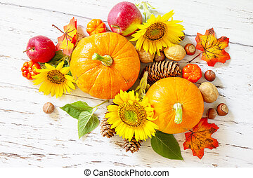 Happy Thanksgiving concept. Pumpkins, sunflowers, apples and fallen leaves on rustic wooden table. Top view flat lay.