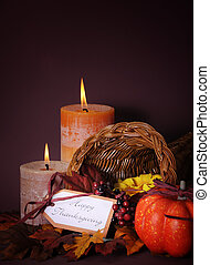 Happy Thanksgiving cornucopia wicker basket with autumn leaves, pumpkin and greeting tag on candlelit background. Vertical with copy space.