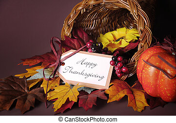 Happy Thanksgiving cornucopia wicker basket with autumn leaves, pumpkin and greeting tag on candlelit background. Close up.