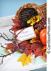 Happy Thanksgiving cornucopia with Autumn Fall leaves, pumpkin, sunflower and berries on white shabby chic tray against a pale blue background. Vertical.