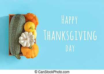 Happy Thanksgiving day text and harvest colored different vegetables gourds pumpkin, zucchini, squash in a wooden box on blue background. Top view Flat lay