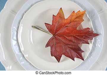Happy Thanksgiving dining table elegant place setting in pale aqua blue and white theme with autumn leaf. Close up.