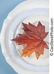 Happy Thanksgiving dining table elegant place setting in pale aqua blue and white theme with autumn leaf. Vertical.
