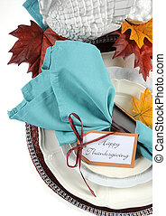 Happy Thanksgiving dining table place setting in Autumn brown and aqua color theme. Vertical.