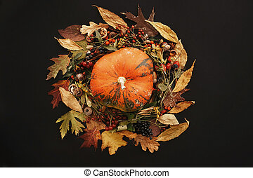 Happy Thanksgiving Flat Lay. Pumpkin in Fall leaves wreath with berries, nuts, acorns, flowers,herbs on black background top view. Seasons greetings. Space for text. Autumn composition