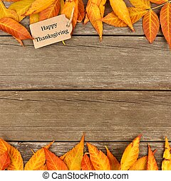 Happy Thanksgiving gift tag with double border of autumn leaves on wood