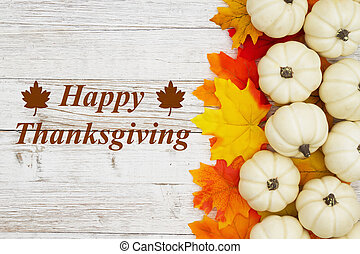 Happy Thanksgiving greeting white pumpkins with fall leaves