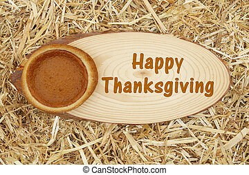 Happy Thanksgiving greeting with a pumpkin pie with straw hay