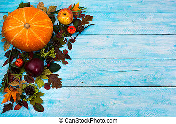 Happy Thanksgiving greeting with fall leaves on blue wooden background