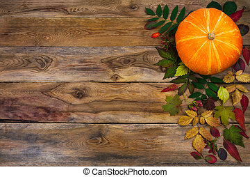 Happy Thanksgiving greeting with fall leaves on rustic wooden background