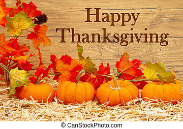 Happy Thanksgiving greeting with orange pumpkins and fall leaves on straw hay