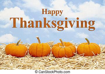 Happy Thanksgiving greeting with orange pumpkins on straw hay