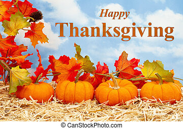 Happy Thanksgiving greeting with orange pumpkins with fall leaves on straw hay