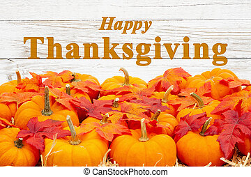 Happy Thanksgiving greeting with orange pumpkins with fall leaves