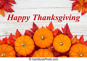 Happy Thanksgiving greeting with red and orange fall leaves and a pumpkins on weathered wood