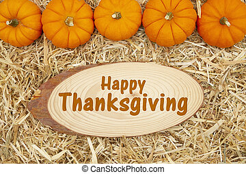 Happy Thanksgiving greeting with straw hay and pumpkins