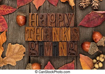 Happy Thanksgiving letterpress with frame of autumn leaves over wood