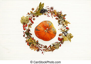 Happy Thanksgiving. Pumpkin in beautiful fall leaves wreath with berries,nuts,acorns, herbs on rustic white background top view. Seasons greetings card mockup. Autumn Flat Lay.