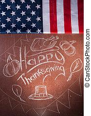 Happy Thanksgiving, written in white chalk on a blackboard,