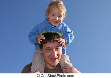 Happy the daddy with a daughter against the sky