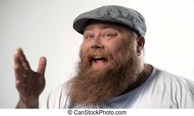 Close up portrait of joyful bearded fat man dancing and laughing. He is shaking his head in rhythm and gesturing by hands. Isolated