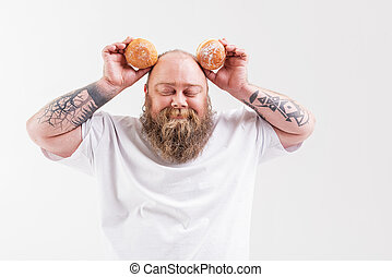 Happy thick guy holding two doughnuts