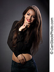 Happy thinking beautiful brunette woman with long hair style in fashion black shirt looking with toothy smiling on dark shadow background